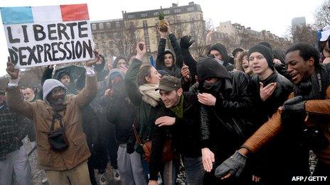 """A man holds a placard reading """"Freedom fo speech"""" as people perform the """"quenelle"""" gesture, popularised by a French controversial comedian, during a demonstration called by the Collective """"Day of Anger"""", supported among others by the conservative Printemps Francais"""