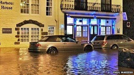 The front of Harbour house with two parked cars out the front