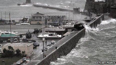 Waves break over the wall at St Peter Port