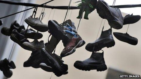 Pairs of shoes hanging from powerlines running between two building in a laneway in Melbourne