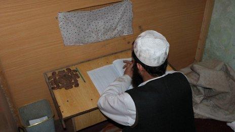 A madrassa teacher instructs pupils from behind a curtain
