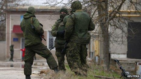 Armed men, believed to be Russian soldiers, stand next to a heavy machine gun as they stand guard at an Ukrainian military base in Yevpatoria