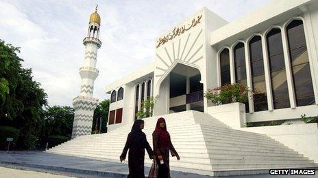 Two women walk past mosque