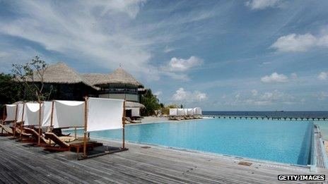 Tourists relax by a pool in the Maldives