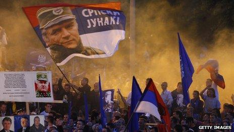 """Supporters of Ratko Mladic wave flags with his picture and reading in Serbian """"Serbian hero"""" during a rally organized by the ultra-nationalist Serbian Radical Party in front of parliament in Belgrade on 11 May 29"""