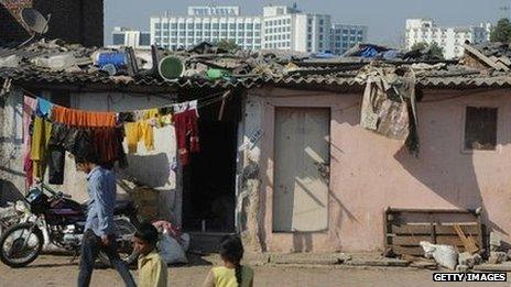 slums and a luxury hotel in Mumbai in the background