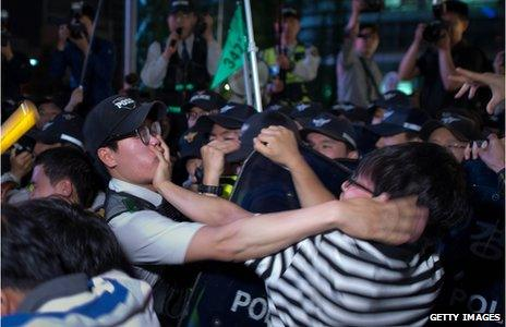 Participants of a candle-lit rally clash with police following vigil for victims of the Sewol ferry during which they also denounced the government response to the disaster
