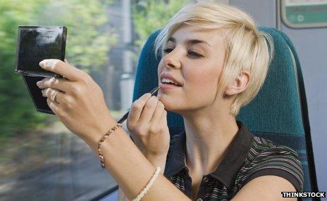Woman applying make-up on train