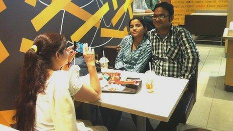 A young couple have their picture taken at a McDonald's restaurant by a friend on her phone