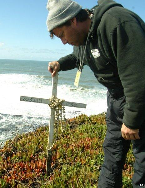 Man stands by memorial cross for Mark Foo