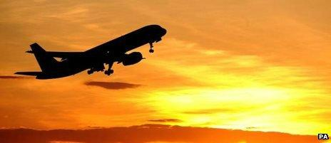 An airliner takes off at sunset