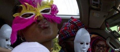 People wearing masks pose as they sit in a vehicle during the first Ugandan gay pride rally since the overturning of a tough anti-homosexuality law, which authorities have appealed, in Entebbe, on 9 August 2014