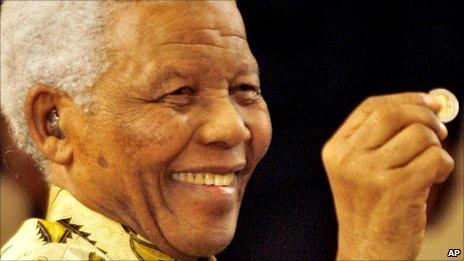 Nelson Mandela holding up a newly minted presidential coin in September 2009
