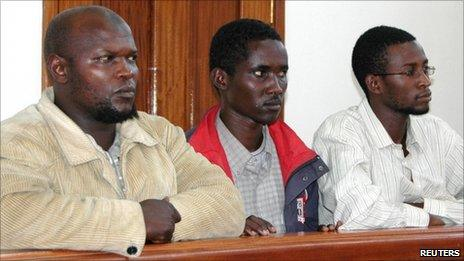 From left to right: Idris Magondu, Hussein Hassan Agad, and Mohamed Adan Abdow, stand in the dock at Nakawa Magistrates Court in Kampala