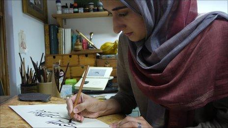 Soraya Syed, an Islamic calligrapher, draws a symbol in ink.