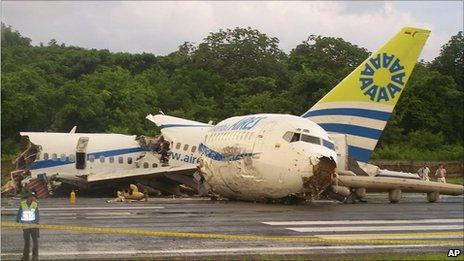 A police officer stands by a crashed plane sitting on the runaway at the airport on San Andres island in Colombia