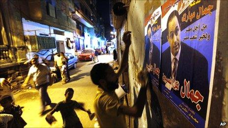 """Egyptian activists of the Popular Coalition to Support Gamal Mubarak hang posters promoting the son of President Hosni Mubarak as the country's next leader, in Cairo, Egypt (21 August 2010). The Arabic reads """"Gamal for all Egyptians""""."""