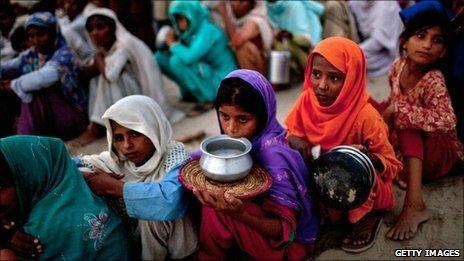Pakistanis queue for food in a flood relief camp near Muzaffargarh in Punjab, Pakistan, on 25 August, 2010