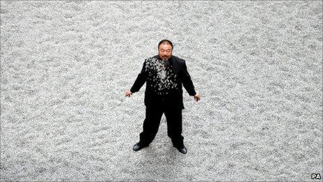 Ai Weiwei standing on seeds