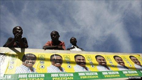 Haitians look at supporters of presidential candidate Jude Celestine march in a rally in Port-au-Prince on 21 November, 2010.
