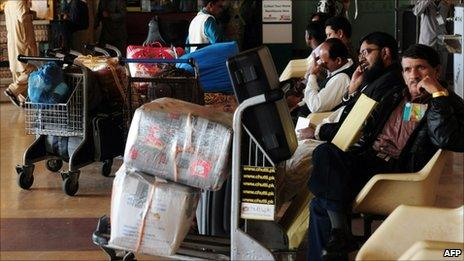 Passengers wait outside the departure lounge of the airport during a strike by employees of the flagship Pakistan International Airlines (PIA) in Karachi on February 8, 2011.