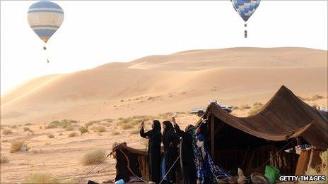 Tuareg women of nomadic tribes take pictures with their mobile phones of hot air balloons flying over the desert of Ghadames, western Libya, September 2009