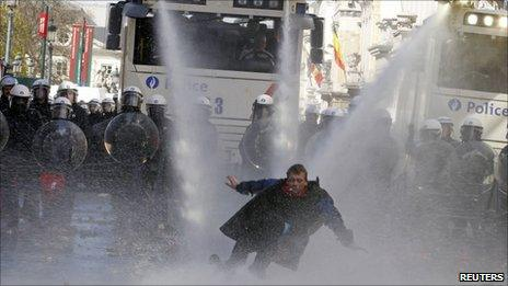 Police direct water cannon at a protester in Brussels, 24 March