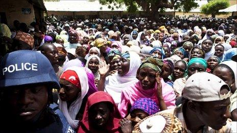 A police officer in riot gear (L) guards a crowded polling station in Kano, northern Nigeria, April 9, 2011.
