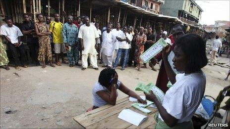 """An electoral officer counts ballots as people watch at the end of the parliamentary elections in Oshodi district in Nigeria""""s commercial capital of Lagos April 9, 2011"""