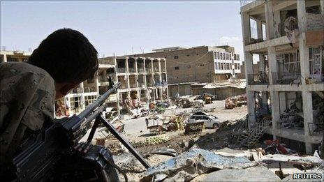"""An Afghan border police keeps watch from a building which was used by the Taliban forces to attack the Kandahar governor""""s office in Kandahar city May 8, 2011"""