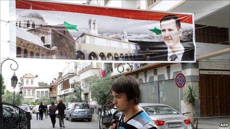 A man walks under a banner of President Bashar al-Assad in Damascus, 30 April, 2011
