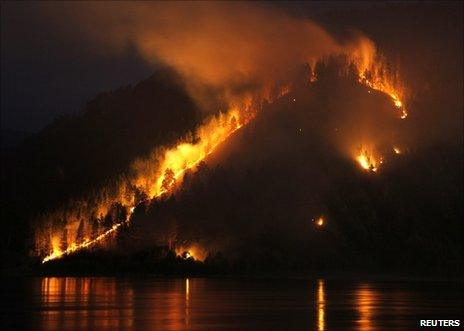 A wildfire burns through woods on a bank of the Yenisei river near Krasnoyarsk, Russia, 21 April