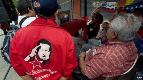 Supporters of Venezuelan President Hugo Chavez in Caracas watch the television broadcast of Mr Chavez's meeting with former Cuban president Fidel Castro - 29 June 2011