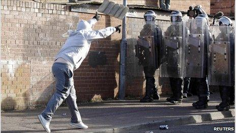 A Nationalist youth throws masonry at police in the Ardoyne area
