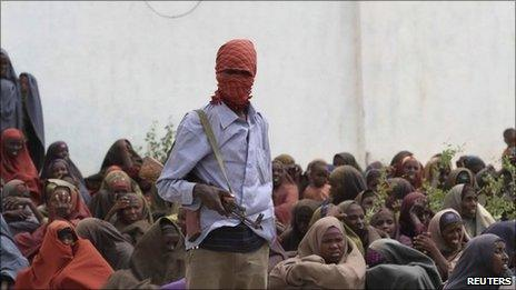 An Al Shabaab soldier stands next to women during food distribution at a displaced persons camp in Shebelle, about 50 km (31 miles) south of the capital Mogadishu, July 6, 2011