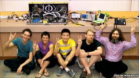 Scientists posing with Eve machine in suitcase