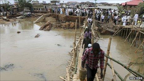 People queue to pass over a makeshift bridge in Ibadan, Nigeria (30 August 2011)