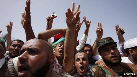 People flash victory signs as they gather at Martyrs Square after Friday prayers in Tripoli September 2