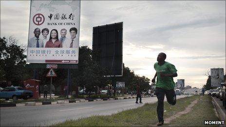 A man runs past a Bank of China billboard in Lusaka, the capital of Zambia