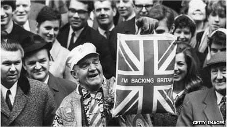 19th March 1968: A man holds up a plastic carrier bag declaring I'm Backing Britain
