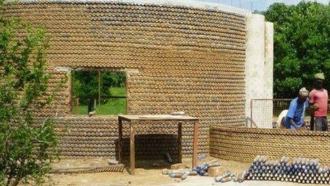 People building a wall made from plastic bottle packed with sand the Nigieran village of Yelwa