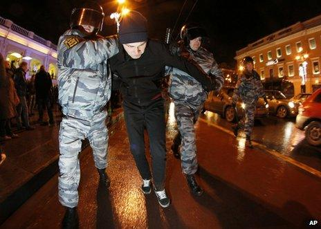 Russian police detain a protester in St Petersburg, 6 December