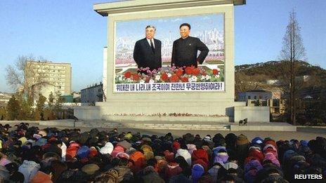 North Koreans bow in front of a statue showing Kim Il-sung and Kim Jong-il in Pyongyang on 19 December 2011