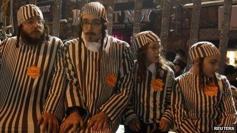 Ultra-Orthodox Jews wear striped black-and-white uniforms associated with Nazi concentration camps at a protest in Jerusalem (31 December 2011)