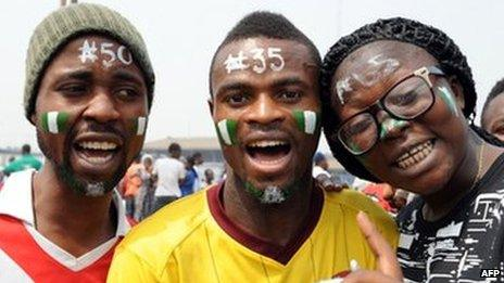 People with their faces painted with the national green and white colours, and different naira denominations on their forehead, pose during a Lagos demonstration