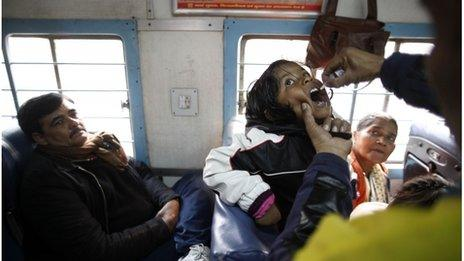 Health workers administer polio drops to children on a train near Ghaziabad, on the outskirts of Delhi, Jan 2012