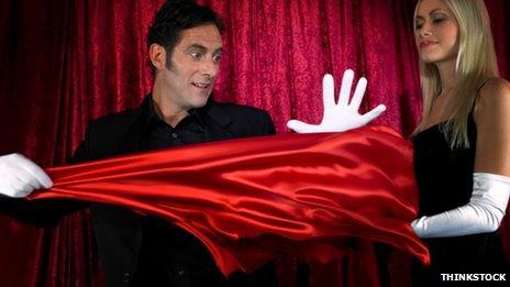 Magician performing a trick involving a red silk cloth
