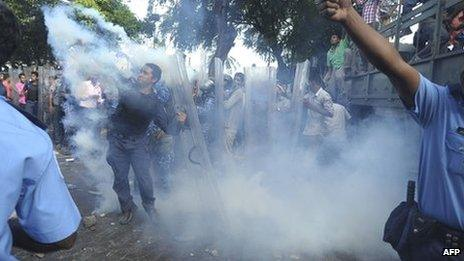 Maldivian police are seen amid a cloud of tear gas as they confront the military in Male in this handout photograph provided by Haveeru News Service