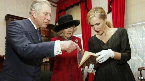 The Prince of Wales, the Duchess of Cornwall and actress Gillian Anderson examine a first edition of one of Dickens's novels