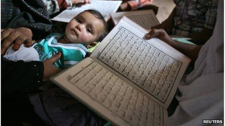 Survivors read the Koran as a child looks on during the commemoration of the 10th anniversary of Godhra riots in the western Indian city of Ahmedabad February 27, 2012